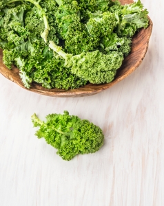 raw  kale preparation on white wooden table